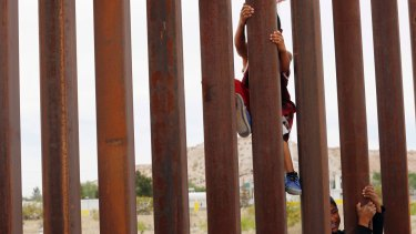Children from Anapra, Mexico, climb a section of the new border wall recently built in New Mexico.