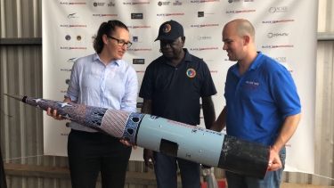 From left to right: Carley Scott, chief executive of ELA, Djawa Yunupingu, traditional owner, from Gumatj Corporation, Blake Nikolic, chief executive of ELA customer Black Sky Aerospace. Painting on the cone of the rocket by painting by artist Dorothy Djakangu Yunupingu.