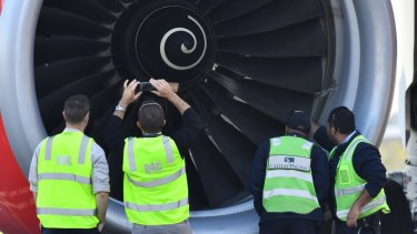 Safety Inspectors look over the engine of AirAsia flight D7207 at Brisbane Airport after a bird strike in July, 2017.