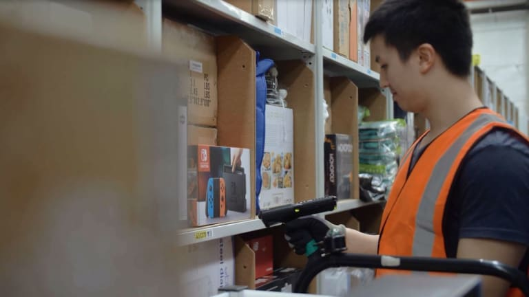An Amazon worker at its Melbourne fulfillment centre with one of the handheld scanners.
