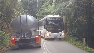 A water carrier passes a tourist bus on Tamborine Mountain.