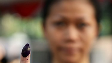 A voter poses for a photograph while showing a finger stained with electoral ink after casting her ballot at a polling station during the presidential election in Jakarta, Indonesia in 2014.