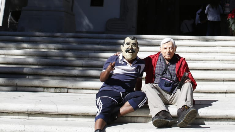 Enedino Camarillo, wearing a mask representing former Mexican President Vicente Fox, and Luis Duque wearing a mask depicting Andres Manuel Lopez Obrador, sit on the front steps of the Casa Miguel Aleman, the presidential residence know as Los Pinos, in Mexico City, on Saturday.