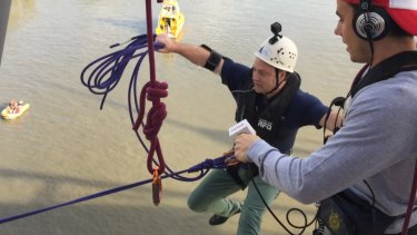 Brisbane Lord Mayor Adrian Schrinner jumps and swings off the Goodwill Bridge for local charity Hear and Say.