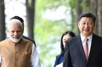 Indian Prime Minister Narendra Modi and Chinese President Xi Jinping walk together in Wuhan, central China, in 2018.