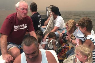 Michael Cripps, left, and son Brett Cripps, in white singlet crammed 12 people and a dog into a small boat and saved their lives as fires raged at Lake Conjola on New Year's Eve.