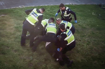 An image from CCTV showing police restraining John outside his home in Preston.