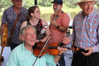 Texas Governor Greg Abbott plays the fiddle as the state's coronavirus cases surge.