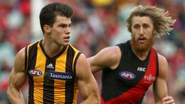 Jaeger O'Meara runs from Essendon's Dyson Heppell.