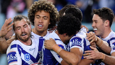 Corey Harawira-Naera of the Bulldogs, centre, celebrates with teammates after scoring at ANZ Stadium.