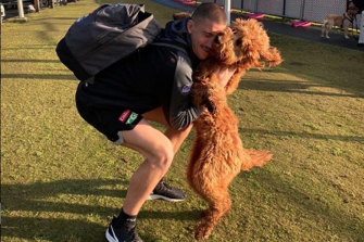 Darcy Cameron farewells his dog before the Pies leave for their hub.