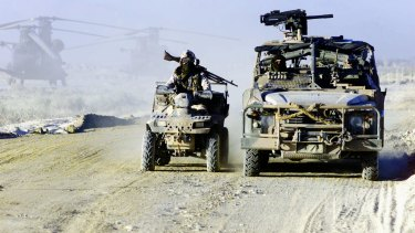 SAS soldiers on their long range patrol vehicle and a Polaris motorbike on duty in Afghanistan.