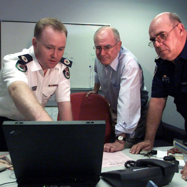 Then prime minister John Howard is briefed by Shane Fitzsimmons and Phil Koperberg of the RFS before visiting the bushfire devastated suburb of Warragamba in 2001.