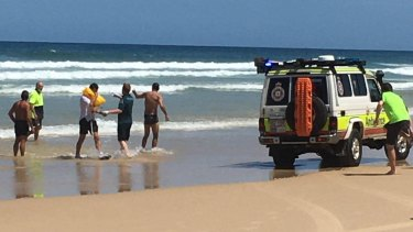 The two men are helped from the water on Fraser Island to an awaiting paramedic.