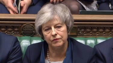 Britain's Prime Minister Theresa May listens to Labour leader Jeremy Corbyn speaking after losing a vote on her Brexit deal.