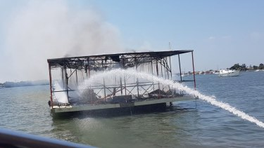 Firefighters worked to control the fire after loading their gear onto the Volunteer Marine Rescue Jacobs Well vessel.