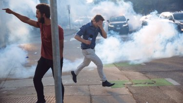 Nine reporter Tim Arvier runs from police tear gas amid protests in Minneapolis over the police killing of George Floyd.