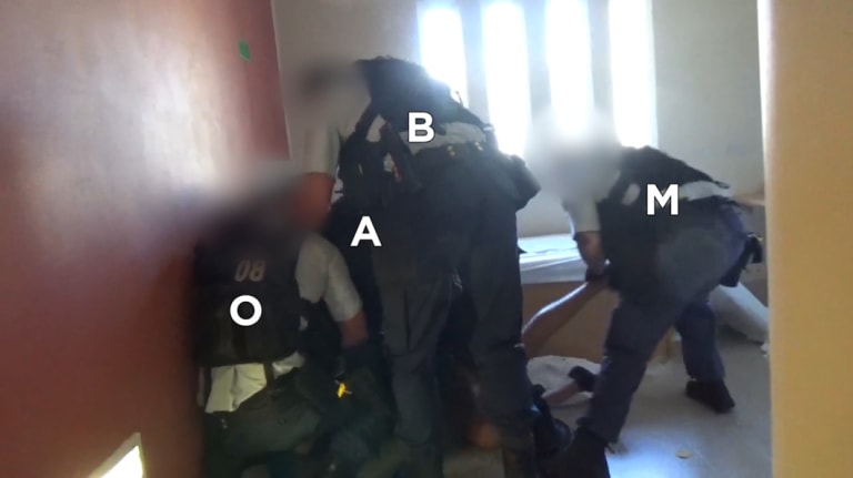 David Dungay being restrained by six officers from the Immediate Action Team before being moved to a different cell.