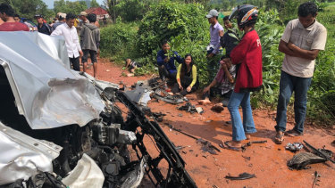 Onlookers stand around the mangled wreckage of Cambodia's Prince Norodom Ranariddh's car.