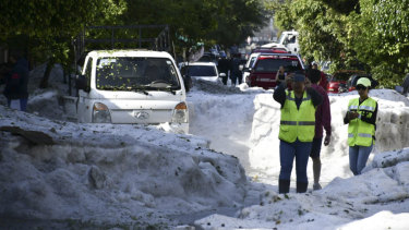 Residents of Guadalajara, Mexico, take pictures of the streets filled with hail.