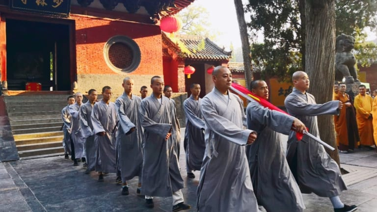 Monks from the Shaolin Temple prepare for the flag raising ceremony.