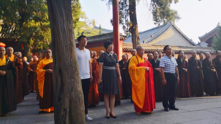 People believed to be officials attend the flag-raising ceremony, the first for the Shaolin Temple.