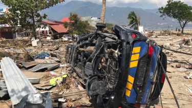 A car lays on its side among the rubble at Talise beach, Palu.