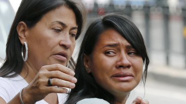Barbara Barca, right, a survivor of the stampede at a crowded nightclub, cries as she leaves police headquarters in Caracas, Venezuela, on Saturday.