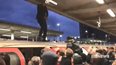 Footage shows angry commuters clashing with a protester who had climbed onto the roof of a train.