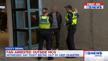 Police speak with a man allegedly involved in the brawl.