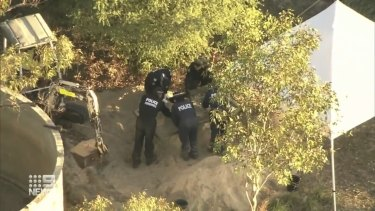 A bobcat and forensic officers combed the back of the property near a water tank most of Tuesday.