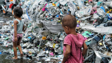 Children in Bangun village in East Java play in their rubbish-filled yard. Some of this is from Australia.