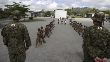 Japanese soldiers watch a march-past by Papua New Guinea's military band.