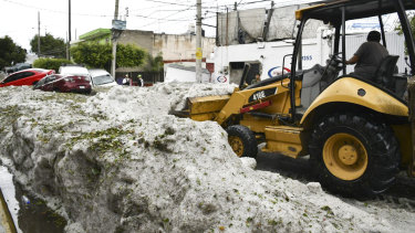 A bulldozer attempts to clear some of the hail.