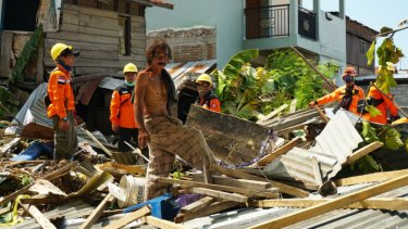 """Daeng Fajar, centre, with an evacuation team looks for the young daughter of a street seller in the rubble at Talise, Palu, Sulawesi.. """"We are not blood related, but she's family."""""""