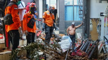 Udin, shirtless, and an East Java evacuation team looks at a spot where they suspected a body is burried.
