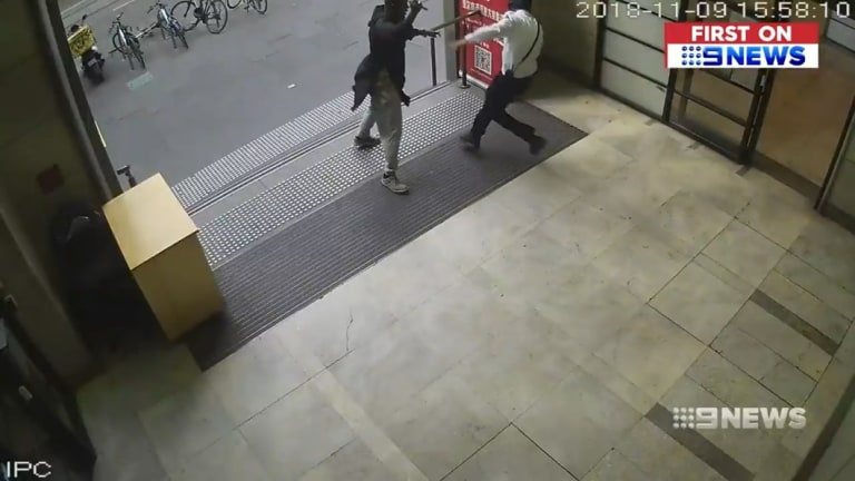 Hassan Khalif Shire Ali continues to lunge at the security guard with the knife.