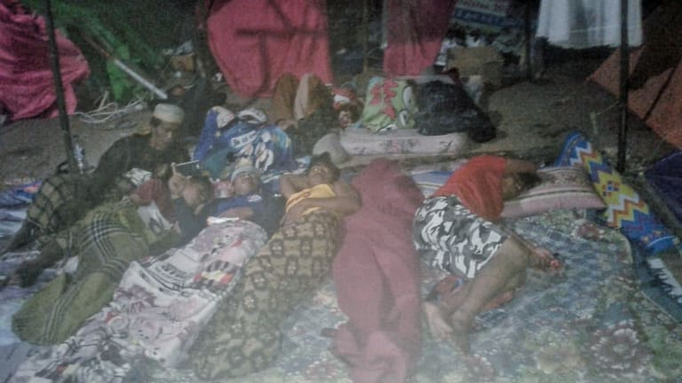 Villagers sleep outside their tents afraid of more aftershocks in Teluk Koombal, Lombok on Sunday.
