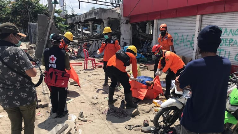 Volunteers retrieve a female body from the ruins of a shop in Talise, Palu, on Tuesday.