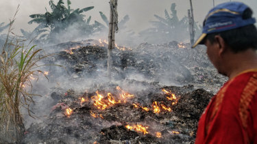 A man watches over the burning of paper company waste because he can't sell it to tofu or cracker factories.