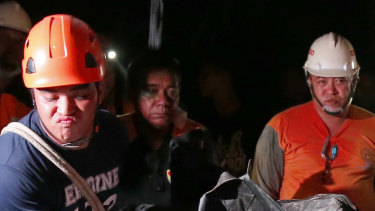 Rescuers load into an ambulance a body of a victim after being dug up from the rubble following a landslide that buried dozens of homes in Naga city, Cebu province central Philippines.