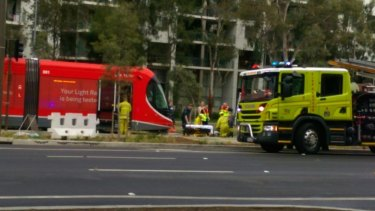 Emergency services tend to a pedestrian after they were hit by a tram on Canberra's light rail network.