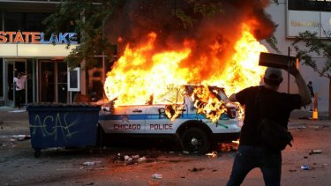A Chicago police vehicle is set on fire during violent protests Saturday, May 30, 2020, as outrage builds over the killing of George Floyd, a black man who died in Minneapolis on May 25 after a police officer pressed his knee into his neck for several minutes. (Ashlee Rezin Garcia/Chicago Sun-Times via AP)