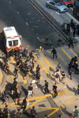 Protesters swarm a police van in Hong Kong on Tuesday.