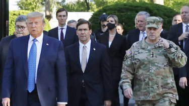Trump's controversial use of troops to clear protesters in June. Trump postures with Chair of the Joint Chiefs of Staff, General Mark Milley, then-secretary of defence Mark Esper is in the middle.