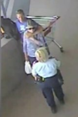 CCTV footage shows the dramatic image of David Clarke holding a knife to the back of a 75-year-old woman, while a police officer intervenes, at a shopping centre in Morisset.