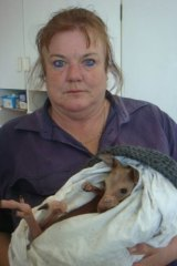 Janine Green holding the sole survivor from a night of senseless slaughter.