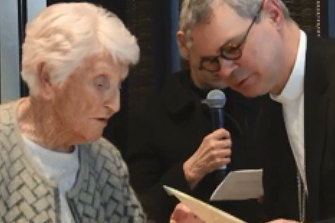 Eileen Piper, 93, shows Catholic archbishop Peter Comensoli a picture of her daughter at his Melbourne Press Club appearance.