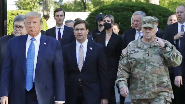 Ivanka Trump, centre wearing a face mask, and Army General Mark Milley, on the right in military fatigues, accompanied Donald Trump and the presidential entourage to St John's church.