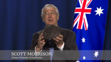 A screen grab of Dick Smith talking about renewable energy, holding a piece of coal and pretending to be Prime Minister Scott Morrison.